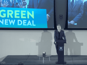 Adam Tooze speaking at a podium with a screen in the back that says Green New Deal