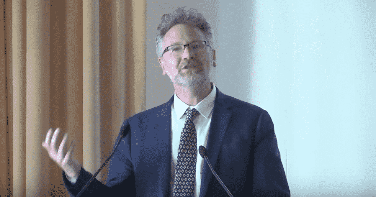 Adam Tooze standing at a podium speaking