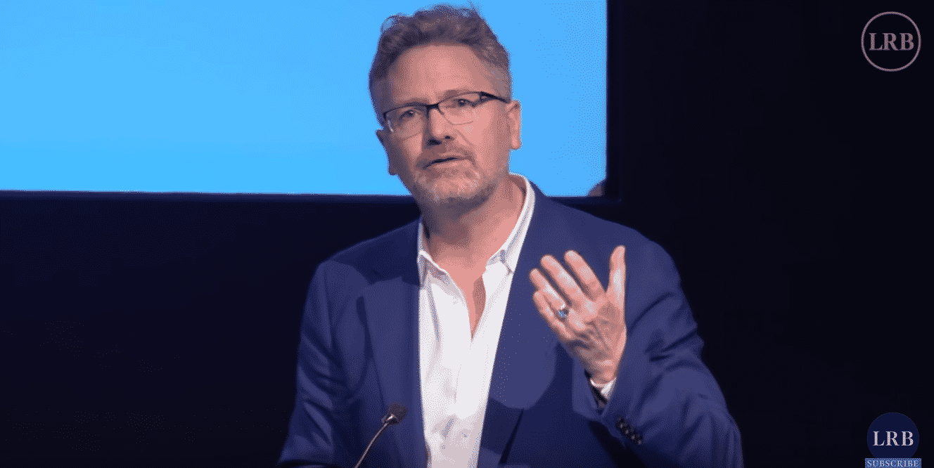 Adam Tooze speaking at a podium, gesturing with one hand